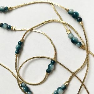 Delicate, gold-tone necklace with blue beads